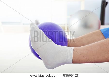 Feet of man doing exercises with rubber ball in clinic