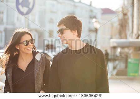 Picture of cheerful young woman walking outdoors with her brother. Looking aside.