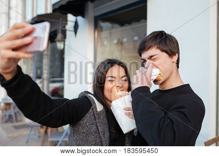 Brother and sister making selfie with closed eyes while eating burgers in the street