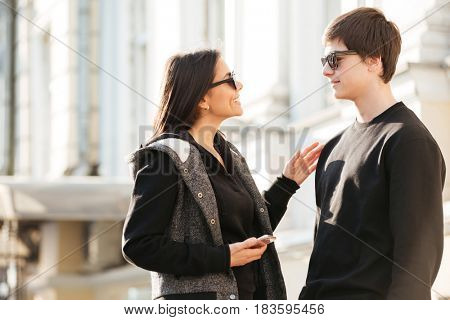 Image of young lady walking outdoors with her brother. Looking aside using mobile phone.