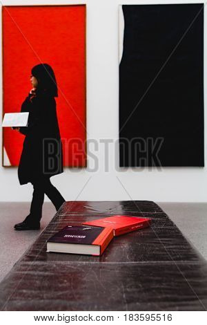 A Woman Walks Past Some Books Laid Out With Color Coordinated Background Artwork.