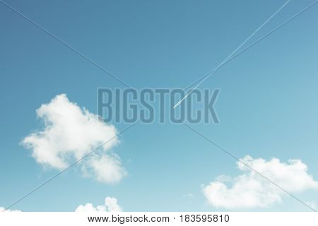 The contrail of a commercial airliner streaks across a teal blue sky with a few puffy fair weather cumulus clouds. Taken from ground level.