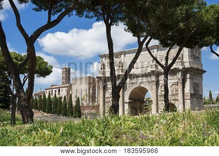 Arch of Constantine and Temple of Venus ancient ruins with green grass in the historic center of Rome