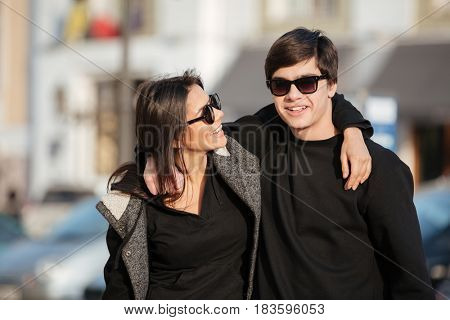 Image of happy young woman walking outdoors with her brother. Looking aside.