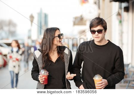 Photo of smiling young lady walking outdoors with her brother drinking juice. Looking aside.