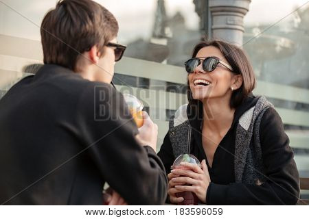 Picture of laughing young lady sitting outdoors with her brother drinking juice. Looking aside. Focus on woman.