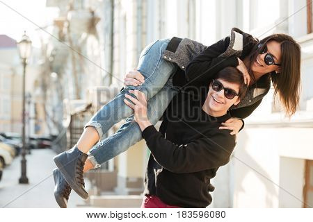 Picture of young woman walking and have fun outdoors with her brother. Looking aside.