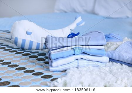 Pile of baby clothes on bed