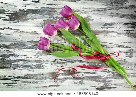 Bouquet of beautiful lilac tulips on shabby wooden background