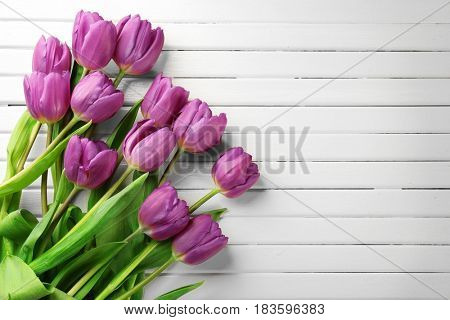 Beautiful lilac tulips on light wooden background