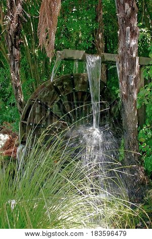 Overshot waterwheel with water supplied by a wooden race with excess water discharging through the side.