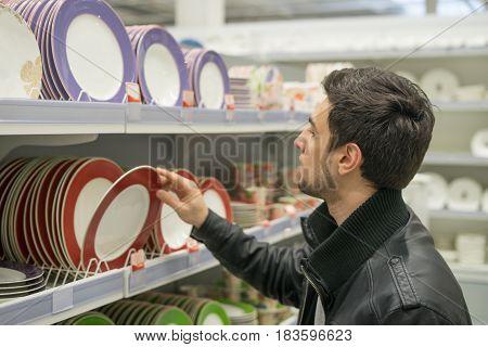 male customer choosing crockery plates in the hypermarket