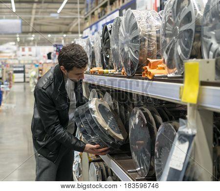 male customer choosing new wheel covers in the supermarket. Car maintenance.