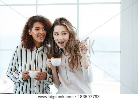 Young smiling women with cups of coffee sharing gossips in cafe