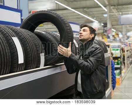 male customer choosing new tires in the supermarket. He is taking tire from shelf
