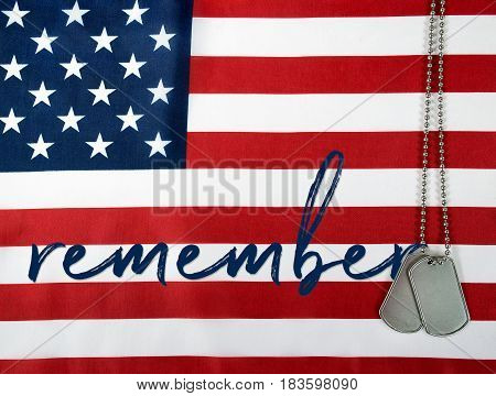word remember and military dog tags on American flag
