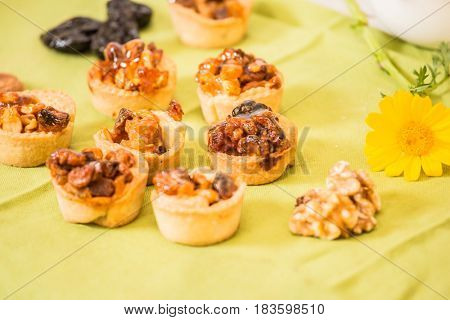 Professional baking. Background -prune. Small portioned tartlet cakes with filling of nuts and dried fruits