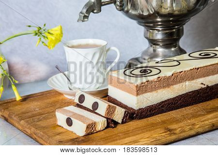Gorgeous holiday cake Three-colate. Three-layered chocolate cake decorated with chocolate patterns. The background is shiny samovar and porcelain cup with tea. Professional bakery