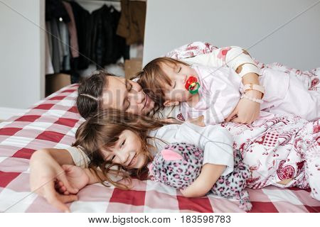 Young pretty woman lying with her cute sleeping children in bed