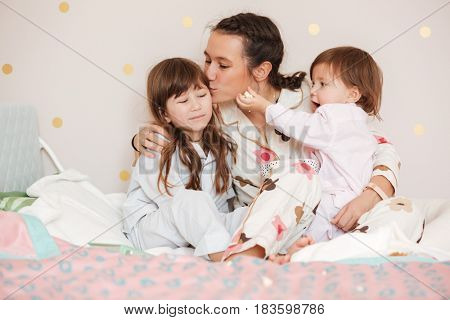 Young mother kissing her daughter while sitting in nursery. Another daughter feed mother