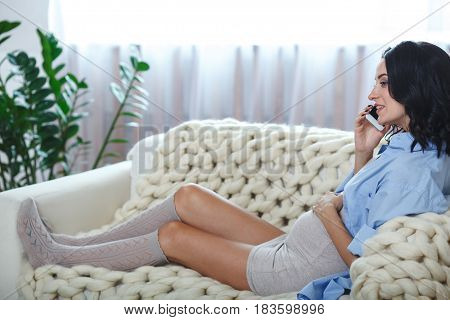 happy pregnant brunette woman calling on smartphone at home, she sitting on couch