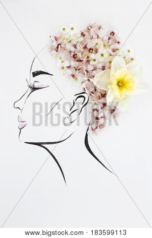 Hand drawn female profile with natural flowers hairstyle isolated over white. Fashion illustration