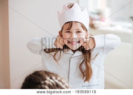 Little joyful girl wearing crown showing tongue at home