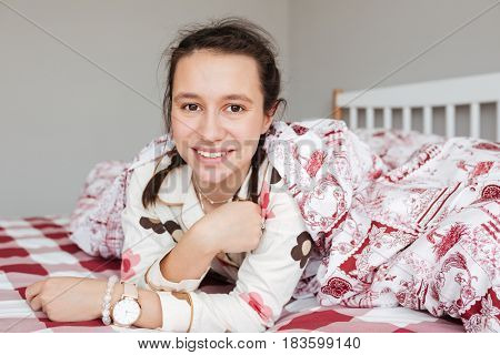 Portrait of young beautiful woman in pajamas lying on bed in bedroom