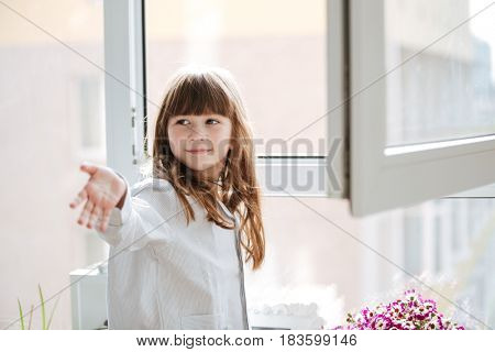 Little smiling girl reaching out hand near window in room