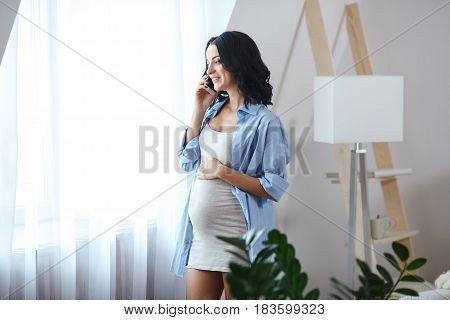 Attractive smiling pregnant brunette woman talking on her smartphone standing near window, horizontal view