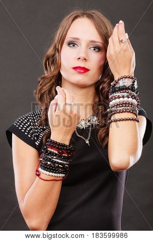 Pretty young woman wearing multiple bracelets jewellery necklace in black elegant evening dress on dark