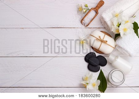 Spa setting and health care items, jasmin aromatic soap, body oil, bath salt, milk, massage stones and towels, on wooden board