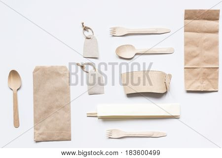 food delivery workdesk with paper bags and flatware on restourant white table background top view mock-up