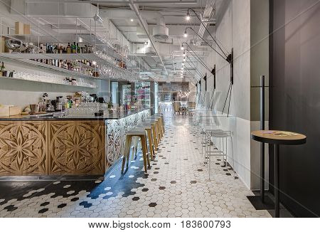 Restaurant in a modern style with gray walls and black and white tiles on the floor. There is a bar with the carved wooden rack, shelves with glasses and bottles, fridge, stools, chairs and tables.