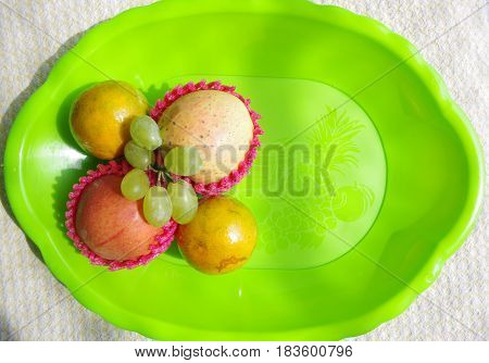 Apples, grapes, and mandarins on a green plastic fruit tray.