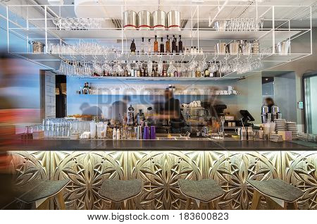 Contemporary bar in the restaurant with a carved wooden rack and stools in front of it. There are shelves with many glasses, cups and bottles coffee machine, juicer, plates and other equipment.