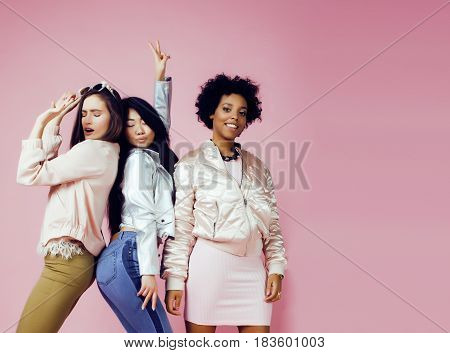 different nation girls with diversuty in skin, hair. Asian, scandinavian, african american cheerful emotional posing on pink background, woman day celebration, lifestyle people concept close up