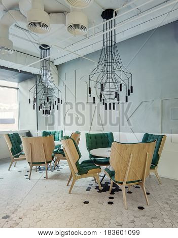Stylish cafe in a loft style with light wall and black and white tiles on the floor. There are white round tables with green armchairs around them, hanging black lamps over them. Vertical.