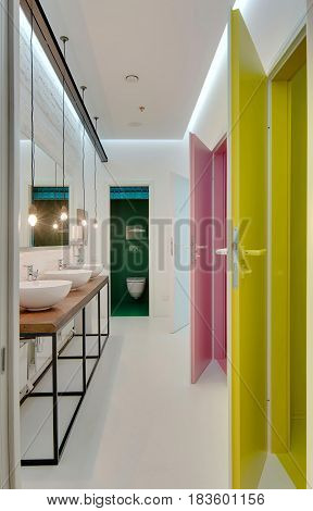 Luminous restroom with white walls and multi-colored doors: cyan, pink, yellow. There is a wooden rack with three sinks, mirror over them, hanging lamps. Far cabin has green walls. Vertical.