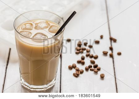 iced coffee with beans for cold summer drink on light wooden table background