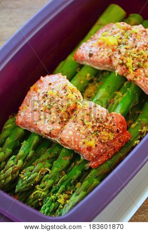 Fresh wild sockeye salmon and organic asparagus spears cooked in silicone steamer. Vertical format with selective focus.