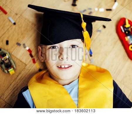 little cute preschooler boy among toys lego at home education in graduate hat smiling posing emotional, lifestyle people concept close up