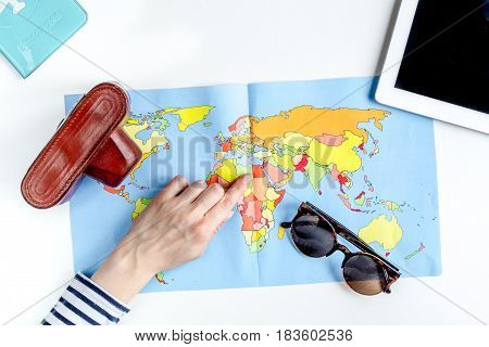 journey planning with tourist outfit and tablet on white table background top view