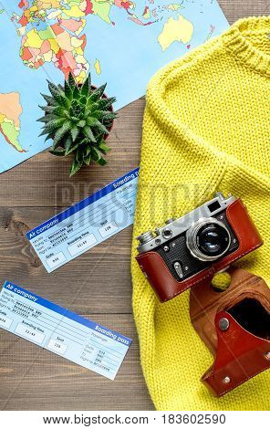 tourist lifestyle with photo camera and flight tickets on wooden table background top view