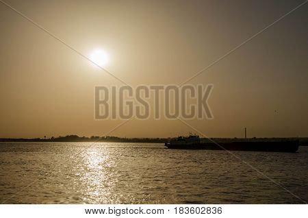 Sunset on the river with barge passing by