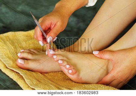 mujer utilizando un removedor de cuticula en sus pies