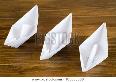 Three origami white paper boats on a wooden table, soft focus.