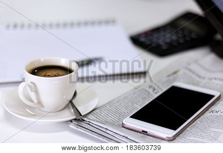 cup of coffee with Newspaper and smartphone on white table.