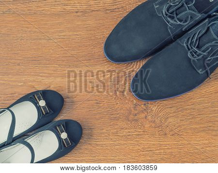 Shoes father and daughter's shoes on the wooden floor. The concept of family happiness.