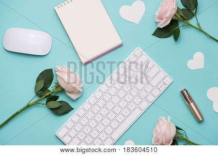 Mother's Day concept. Pink roses with gift box on woman office desk. Open notebook for copy space.